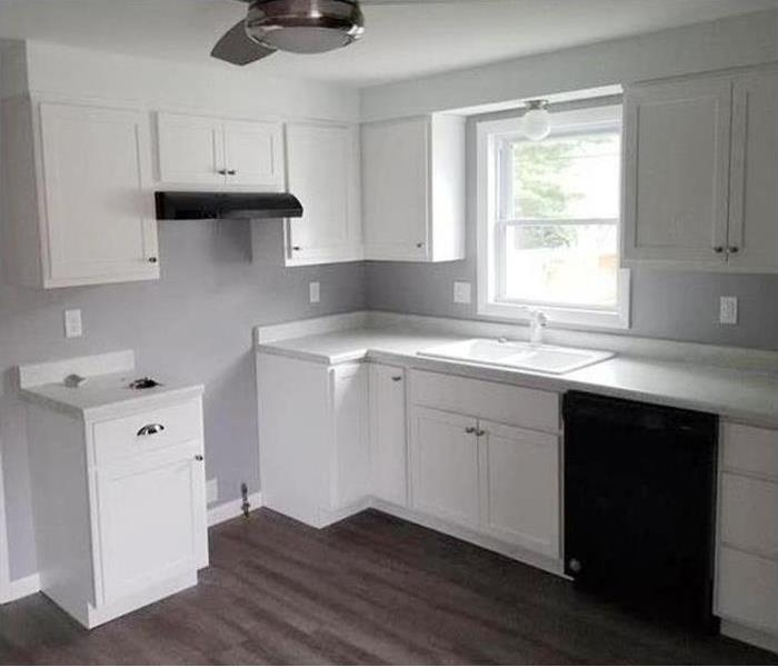 a brand new kitchen with white cabinets and gray flooring
