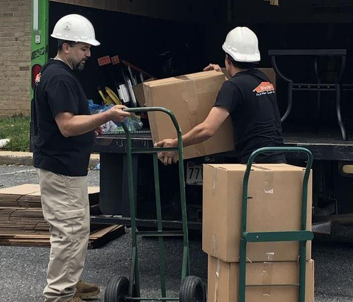 Two SERVPRO employees unloading a truck.